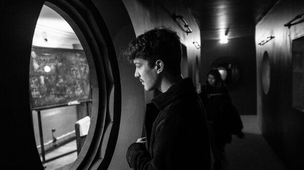 Посетитель осматривает через иллюминатор иммерсивную инсталляцию, воспроизводящую обстановку Института DAU, на площадке арт-проекта DAU в Национальном центре искусства и культуры Помпиду в Париже