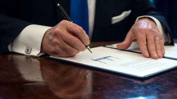 Президент США Дональд Трамп подписывает документ в Овальном кабинете Белого дома