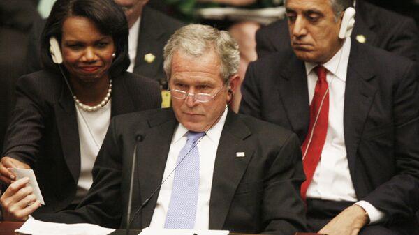 Президент США Джордж Буш показывает записку государственному секретарю Кондолизе Райс на саммите ООН в Нью-Йорке. 2005 год