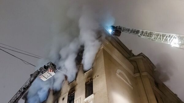 Сотрудники пожарной службы тушат пожар в здании на Никитском бульваре в центре Москвы