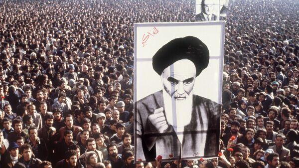 Протестующие в портретом аятоллы Хомейни во время демонстрации против шаха Пехлеви в Тегеране Иран. 16 января 1979