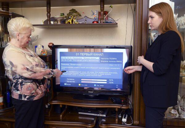 Волонтер помогает жительнице города Пенза подключить устройство захвата цифрового сигнала для ТВ приемника