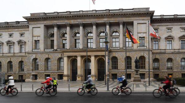 Велосипедисты едут мимо здания Палаты депутатов Берлина