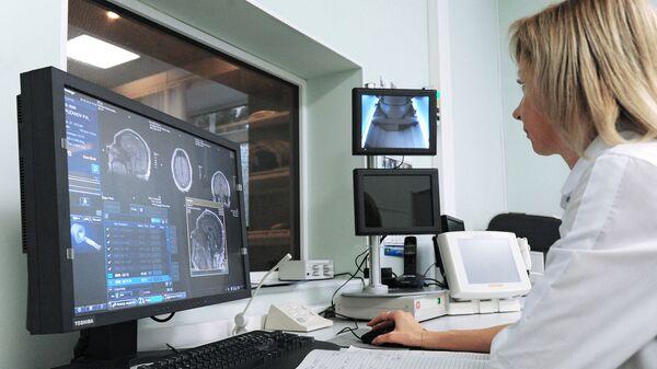 Врач кабинета МРТ проводит процедуру магнитно-резонансной терапии