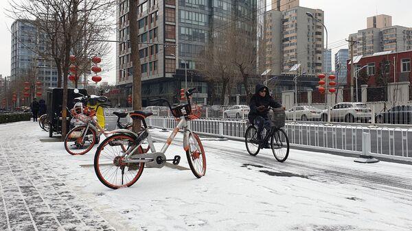Женщина на велосипеде на одной из улиц Пекина