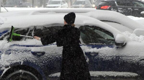 Женщина чистит автомобиль от снега