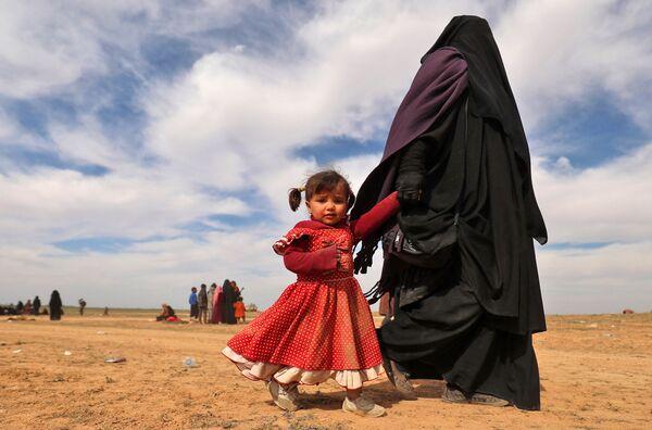 Женщина с ребенком бегут из лагеря беженцев в деревне Багуз, спасаясь от террористов в провинции Дейр-эз-Зор