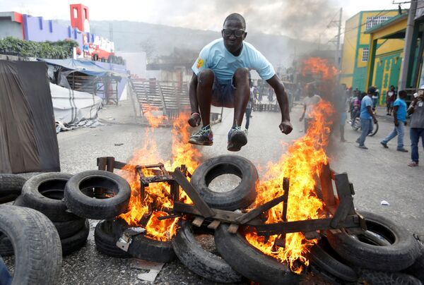 Протестующий перепрыгивает через горящую баррикаду во время акции протеста против правительства на улицах Порт-о-Пренса, Гаити