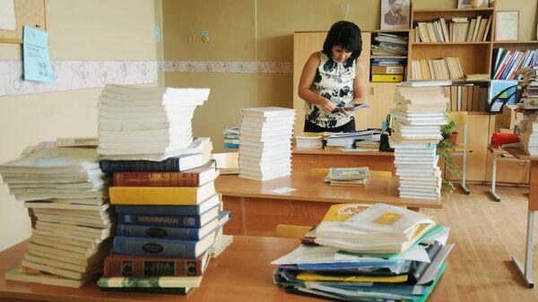 Учительница сортирует учебники в классе