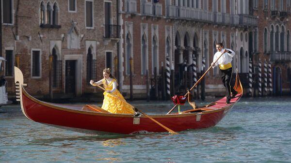 Люди на гондоле во время парада, посвященного началу карнавального сезона в Венеции