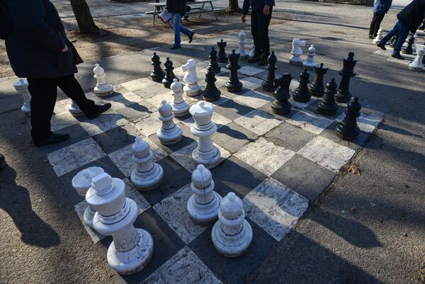 Люди играют в шахматы в парке Бастион в Женеве