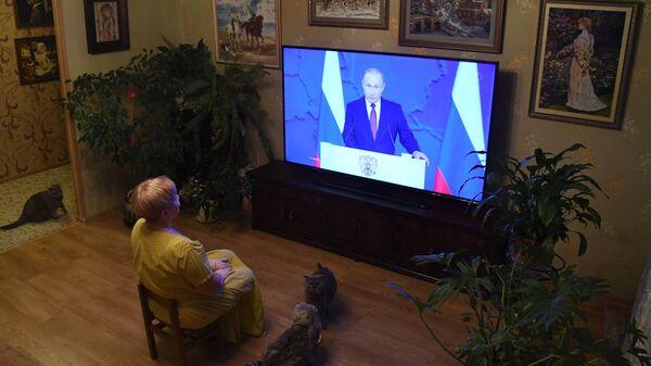 Жительница Владивостока смотрит телевизионную трансляцию ежегодного послания президента РФ Владимира Путина к Федеральному собранию
