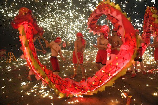 Артисты исполняют танец дракона во время Праздника фонарей в Китае