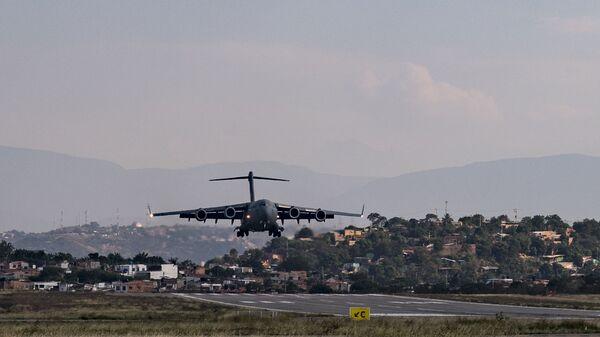 Американский военно-транспортный самолет C-17 Globemaster III  заходит на посадку в колумбийской Кукуте на границе с Венесуэлой