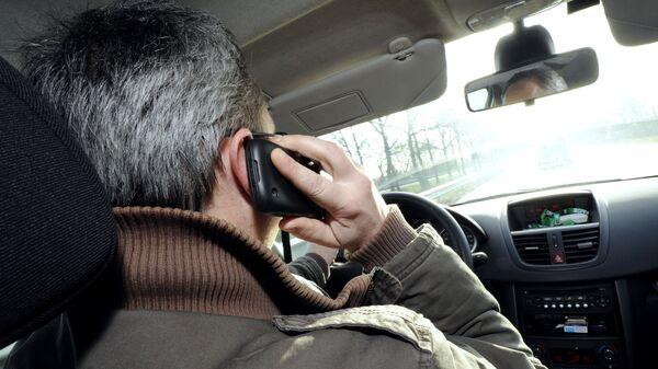 Мужчина разговаривает по телефону за рулем автомобиля