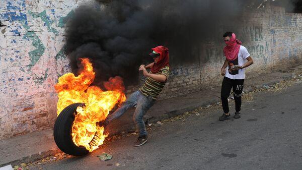 Демонстранты во время столкновений с полицией в Венесуэле