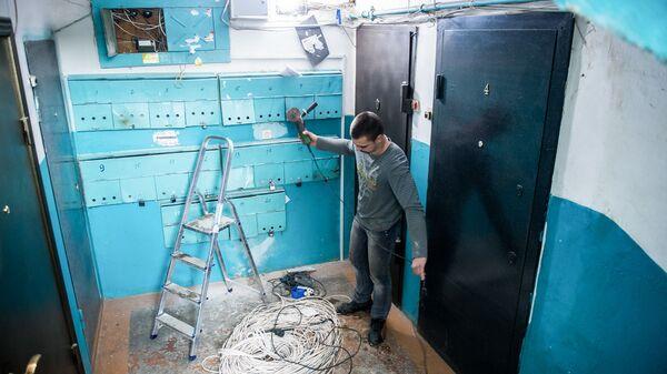Рабочие меняют электропроводку в подъезде жилого дома
