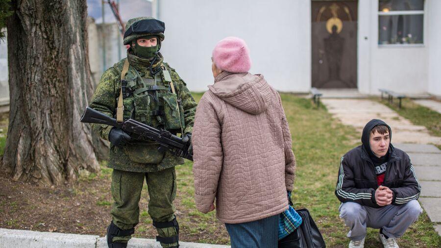 Местная жительница разговаривает с военнослужащим в селе Перевальное недалеко от Симферополя
