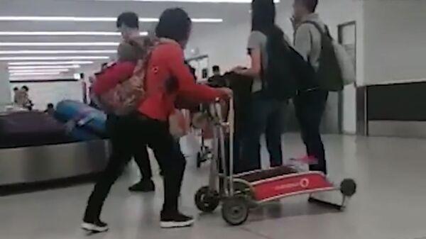 Женщина с тележкой в аэропорту Сиднея