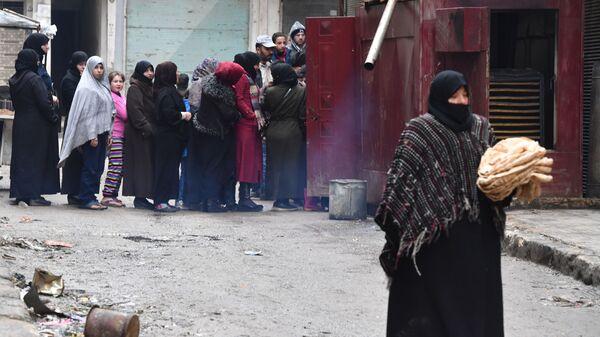 Местные жители в очереди за хлебом на одной из улиц в Алеппо