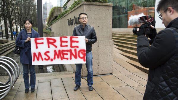 Люди с плакатом на улице Ванкувера в Канаде, выражающие поддержку финансовому директору компании Huawei Мэн Ваньчжоу