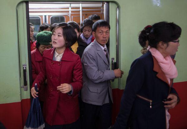 Пассажиры выходят из вагона поезда в метро в Пхеньяне