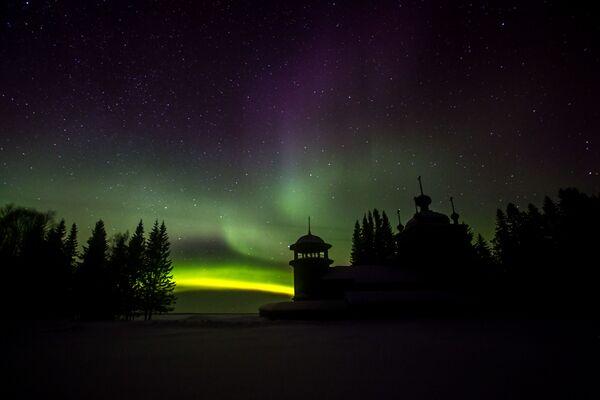 Ночь и северное полярное сияние над мужским монастырем Свято-Ильинская Водлозерская Пустынь на острове Малый Колгостров озера Водлозеро в Карелии