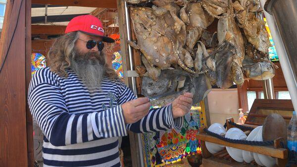 Капитан демонстрирует одну из пойманных рыб на своей прогулочной яхте в морском порту в Сочи