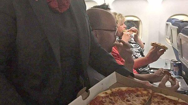 Член экипажа угощает пассажиров пиццей, заказанной капитаном