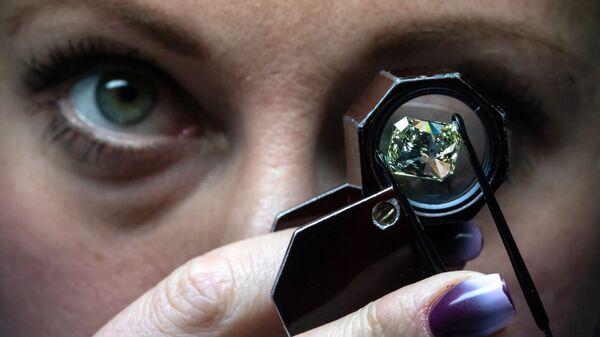 Сотрудница производит оценку бриллианта в цехе технического контроля и оценки ООО Бриллианты Алроса в Москве