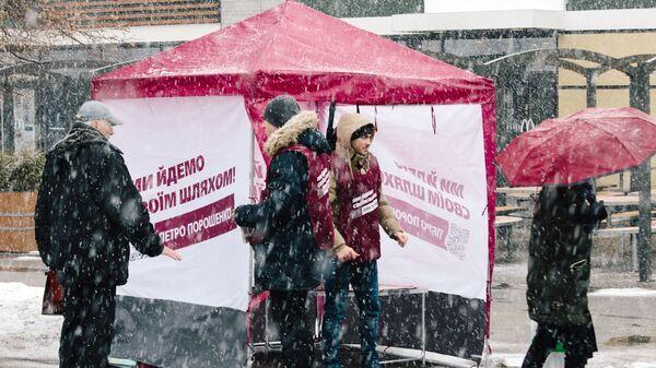 Прохожие и волонтеры у агитационной палатки с печатной продукцией кандидата и действующего президента Украины Петра Порошенко