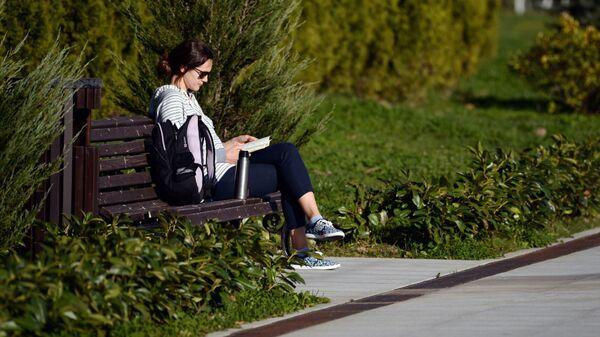 Девушка читает книгу на набережной реки Мзымта