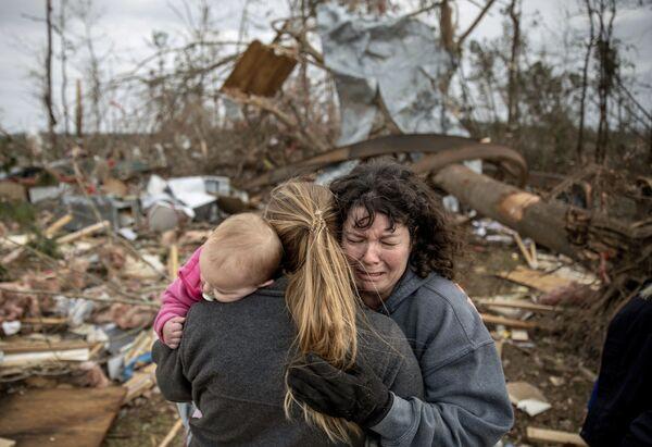 Пострадавшие от торнадо в штате Алабама возле разрушенного дома