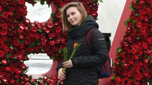 Девушка с тюльпаном, подаренным волонтерами движения Мосволонтер в рамках добровольческой акции Вам, любимые! , в парке Зарядье в Москве