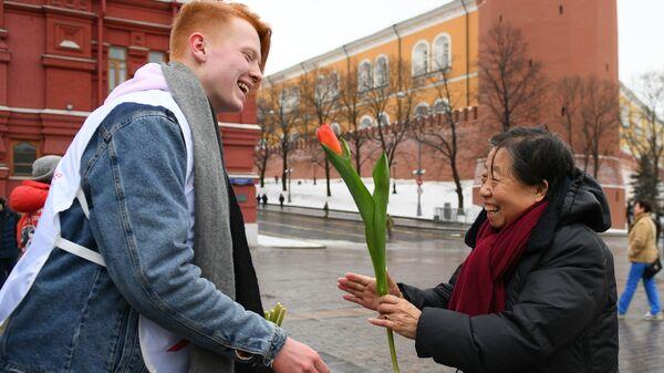 Волонтер движения Мосволонтер в рамках добровольческой акции Вам, любимые! дарит цветы и поздравляет женщину с Международным женским днем на Красной площади