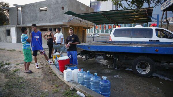 Жители Каракаса стоят в очереди, чтобы набрать воду в бутылки и канистры