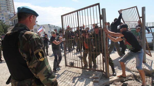 Народные дружинники демонтируют забор на входе на пляж в поселке Парковое под Ялтой