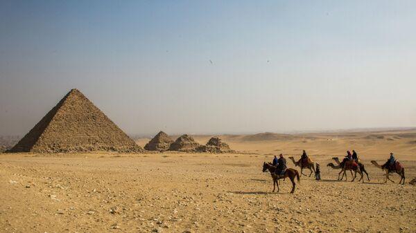 Группа туристов верхом на лошадях и верблюдах во время экскурсии к древнеегипетским пирамидам в Эль-Гизе, пригороде Каира