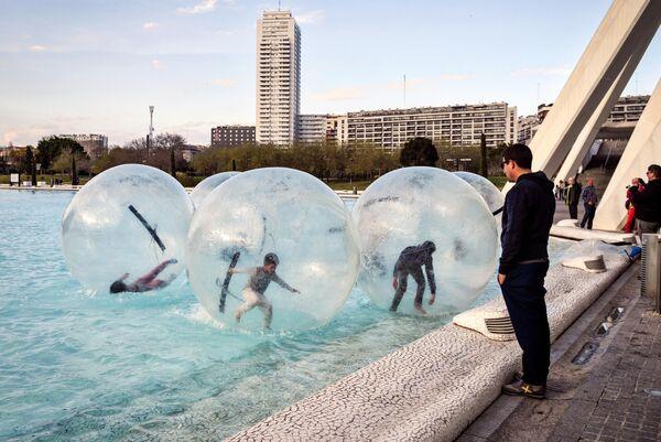 Дети катаются в аквазорбах в бассейне на территории архитектурного комплекса Город Науки и Искусств в Валенсии