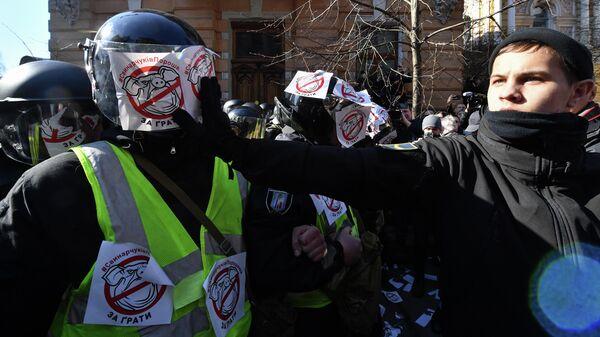 Активисты Национального корпуса клеят стикеры с изображением свиньи на сотрудников полиции во время акции протеста в Киеве, Украина