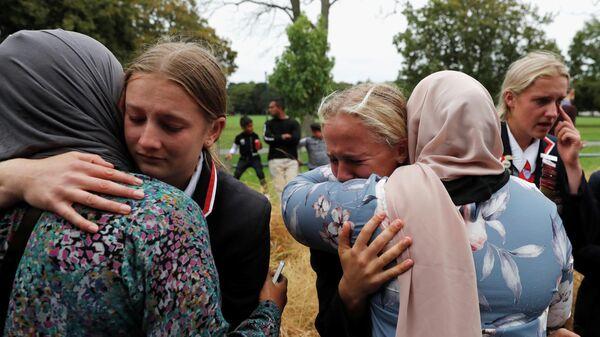 Старшеклассники христианской школы обнимают мусульманок, ждущих новостей о своих родственниках, пострадавших при стрельбе в мечете, Крайчестер, новая Зеландия. 18 марта 2019