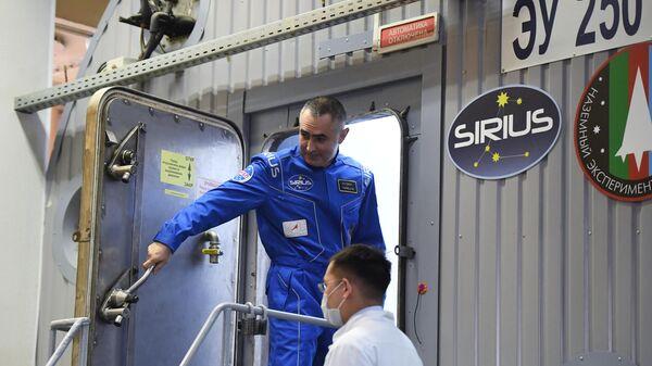 Участник эксперимента по моделированию полета на Луну SIRIUS-19 Евгений Тарелкин заходит внутрь наземного экспериментального комплекса. 19 марта 2019