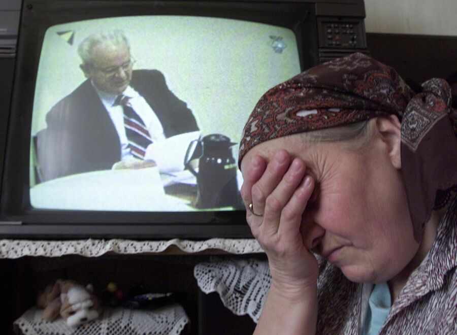Боснийская женщина плачет, наблюдая по телевизору за трибуналом над Слободаном Милошевичем. 14 февраля 2002