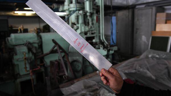 Заведующий кафедрой обработки металлов давлением Института цветных металлов и материаловедении СФУ Сергей Сидельников демонстрирует листовой прокат, полученный из алюминиевого сплава, экономно легированного скандием.