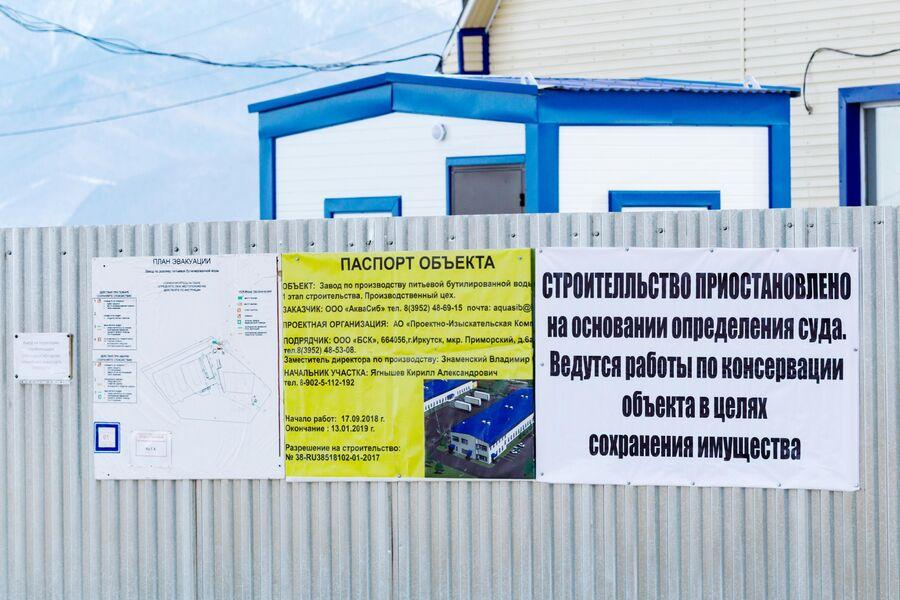 Информационные плакаты на заборе завода по производству питьевой бутилированной воды ООО Аквасиб в поселке Култук