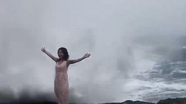 Кадр из видео, в котором девушку захлестнула огромная волна