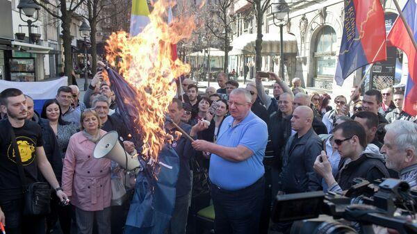 Воислав Сесель, лидер ультранационалистической сербской радикальной партии, держит горящий флаг НАТО на акции протеста в Белграде, Сербия. 24 марта 2019