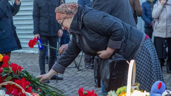 Женщина возлагает цветы к мемориалу в память о жертвах пожара в торгово-развлекательном центре Зимняя вишня в Кемерово