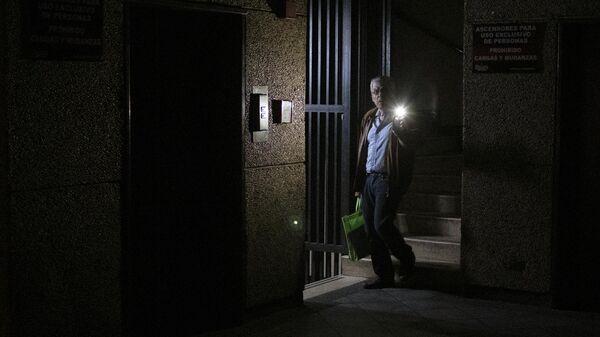 Мужчина в здании во время отключения электроэнергии в Каракасе