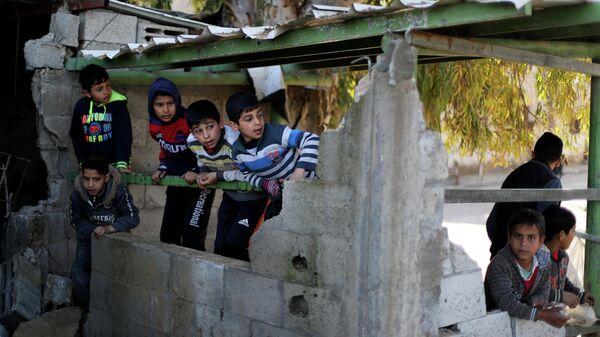 Палестинские мальчики в здании, разрушенном в результате ударов Израиля